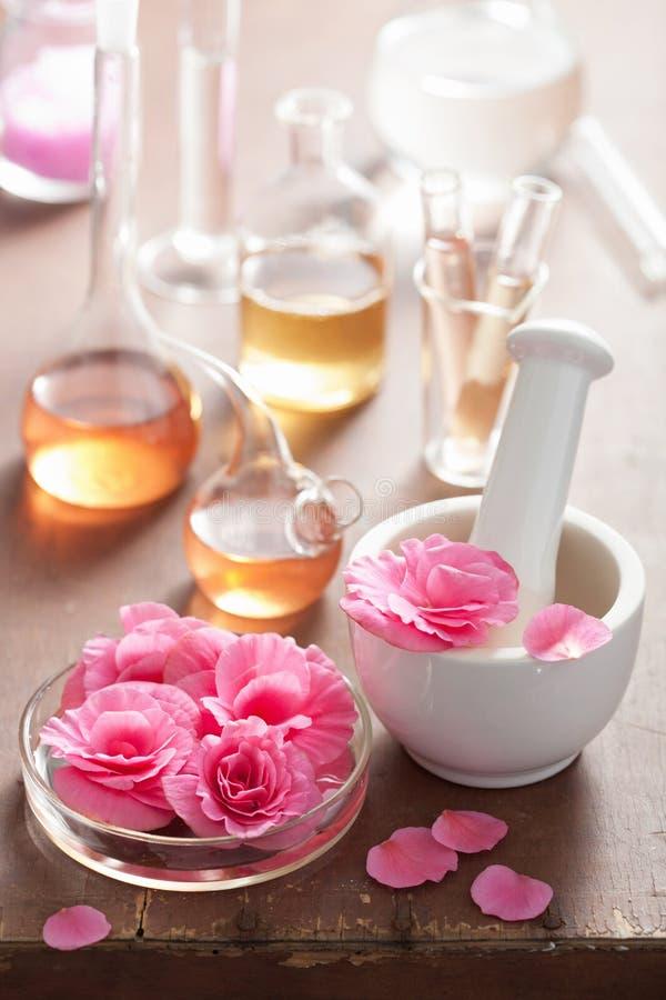 Aromatherapie und Alchimie mit rosa Blumen lizenzfreies stockbild