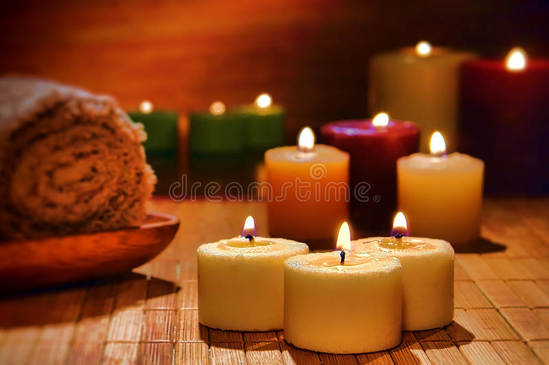 Aromatherapy Candles Spiritual Relaxation in a Spa. Aromatherapy votive candles burning with a soft glow flame in dim light for a spiritual and wellness