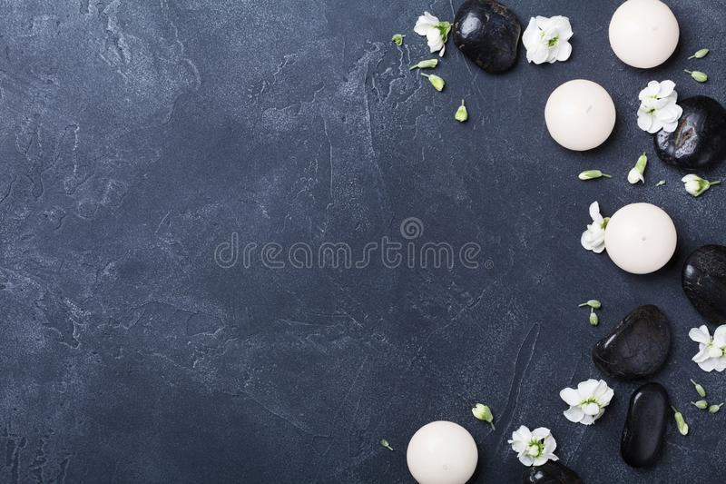 Aromatherapy composition decorated flowers on black stone background top view. Beauty treatment, spa and relaxation concept. Flat lay stock image