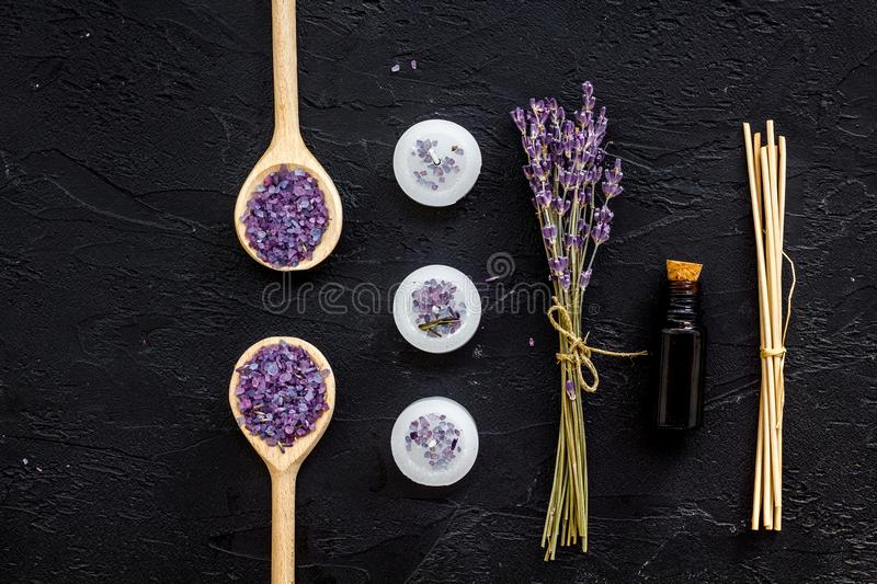 Aromatherapy for relax concept. Lavender branch, spa salt, oil and candles on black background top view stock image