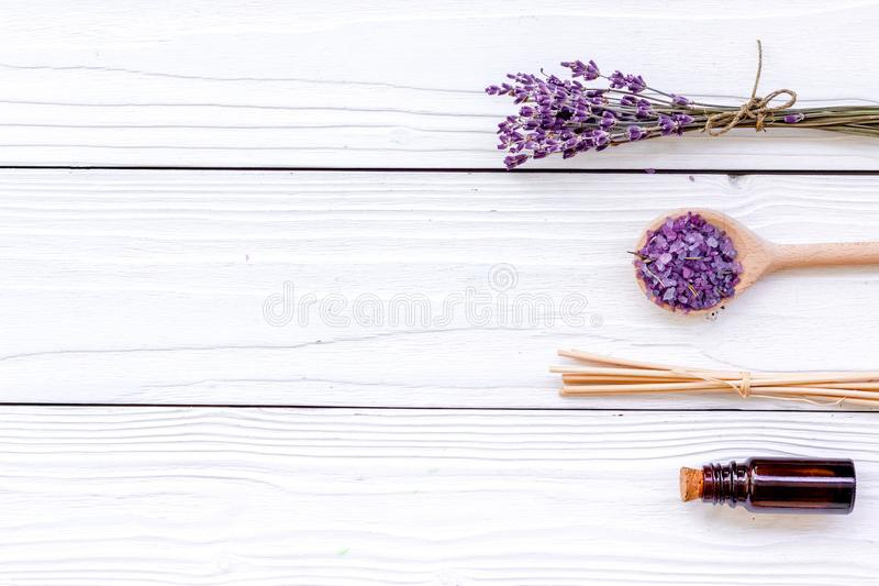 Aromatherapy for relax concept. Lavender branch, spa salt and oil on white wooden background top view copyspace royalty free stock photo