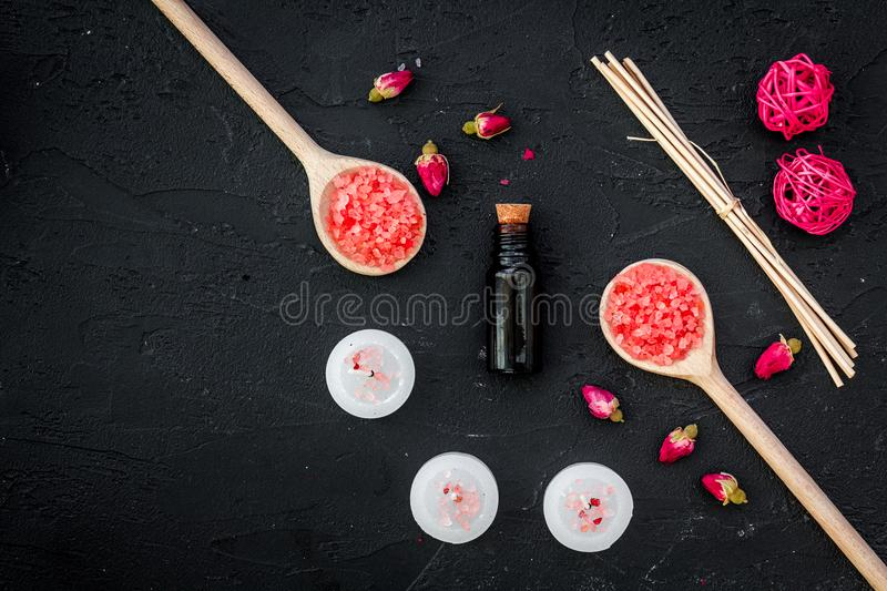 Aromatherapy for relax concept. Rose buds, spa salt, candles and oil on black background top view copyspace stock photos