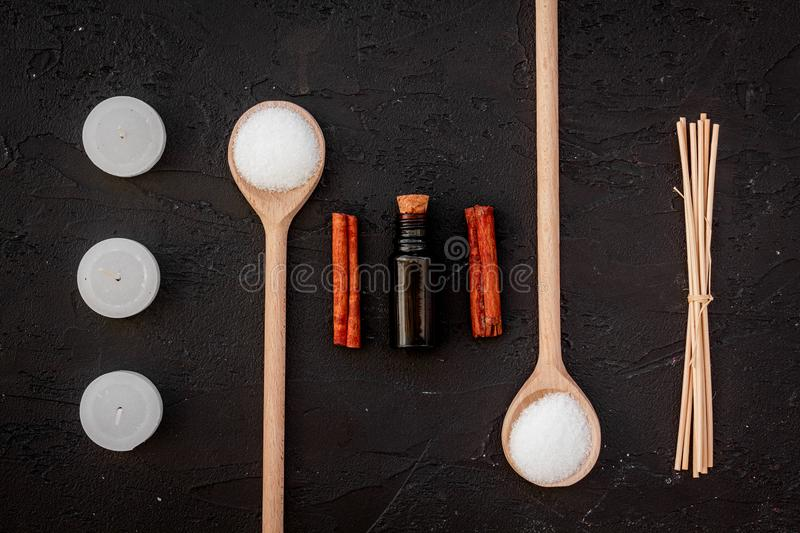 Aromatherapy for relax concept. Spa salt, candles and oil with spices cinnamon on black background top view royalty free stock image