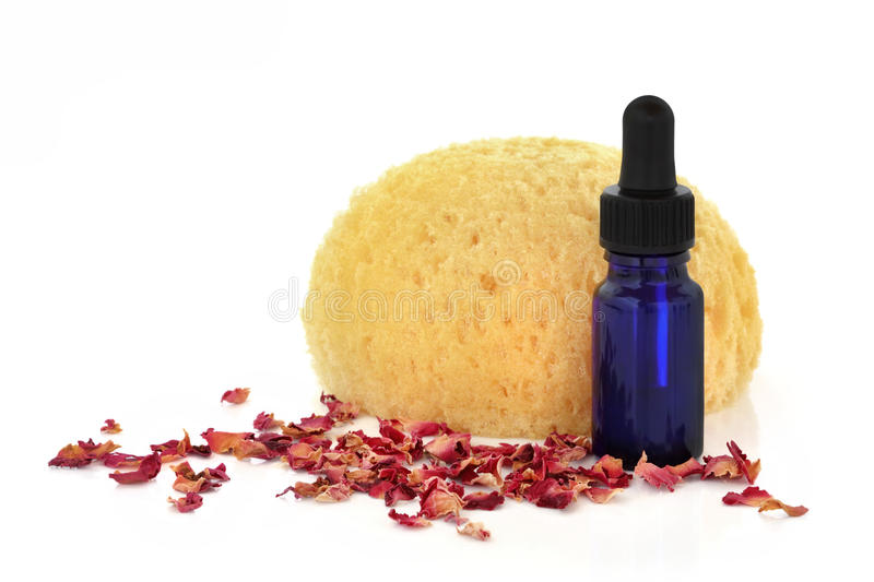 Aromatherapy Rose Essence. Aromatherapy essential oil glass bottle with scattered rose petals and a bath sponge, over white background royalty free stock photography