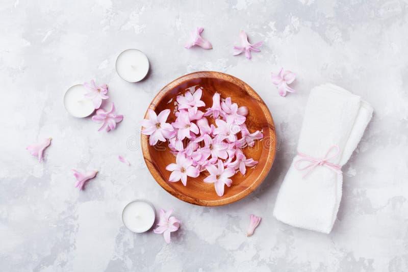 Aromatherapy, schoonheid en kuuroordachtergrond met geparfumeerd roze bloemenwater in houten kom en kaarsen op steenlijst Vlak le stock fotografie