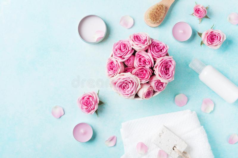 Aromatherapy, spa, beauty background with roses flowers, cosmetics and candles on blue table. Flat lay style stock image
