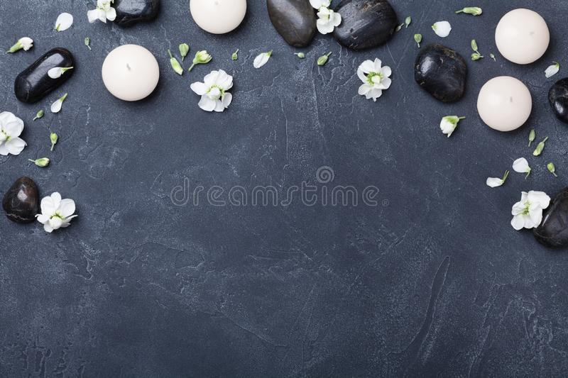 Aromatherapy and spa composition decorated flowers on black stone background top view. Beauty treatment and relaxation concept. Flat lay royalty free stock image