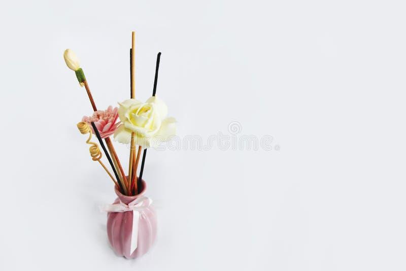 Aromatherapy sticks and decorative artificial flowers in pink ceramic vase. Aromatherapy sticks and decorative artificial flowers in a pink ceramic vase stock image