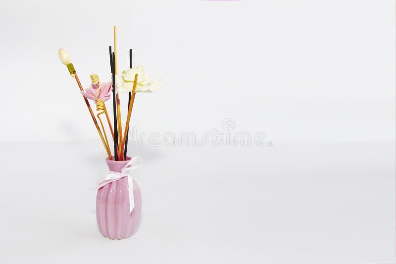 Aromatherapy sticks and decorative artificial flowers in pink ceramic vase. Aromatherapy sticks and decorative artificial flowers in a pink ceramic vase royalty free stock photo