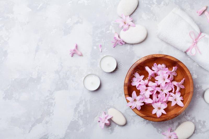 Aromatherapy, zdrój, piękna tło z masażu otoczakiem, perfumujący kwiaty woda i świeczki na kamiennym stołowym odgórnym widoku, Mi zdjęcia stock