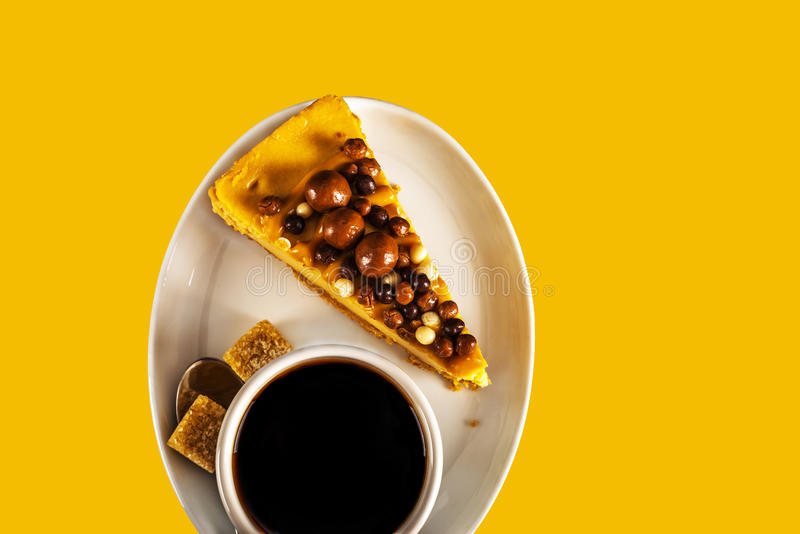 Aromatic black coffee in white cup with cheesecake on white saucer, brown sugar, teaspoon, yellow backround. Tasty set royalty free stock photography