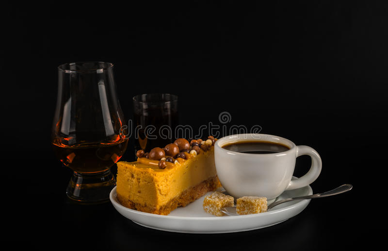 Aromatic black coffee in white cup with cheesecake on white saucer, single malt, and coffee liqueur, brown sugar, teaspoon, black stock image