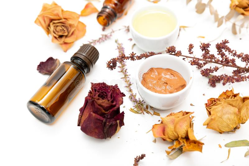 Aromatic botanical cosmetics. Dried herbs flowers mixture, facial mud clay mask, oils, applying brush. Holistic herbal skincare. Beauty hack royalty free stock image