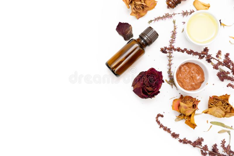 Aromatic botanical cosmetics. Dried herbs flowers mixture, facial mud clay mask, oils, applying brush. Holistic herbal skincare. Beauty hack stock images