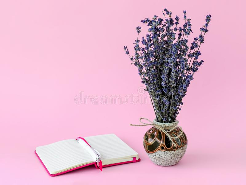 Aromatic bouquet of dry lavender in a beautiful ceramic vase and white ballpoint pen on the opened lined paper notepad in a pink royalty free stock images