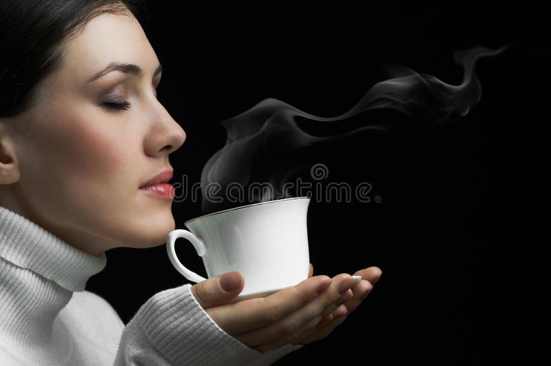 Aromatic coffee. Woman with an aromatic coffee in hands