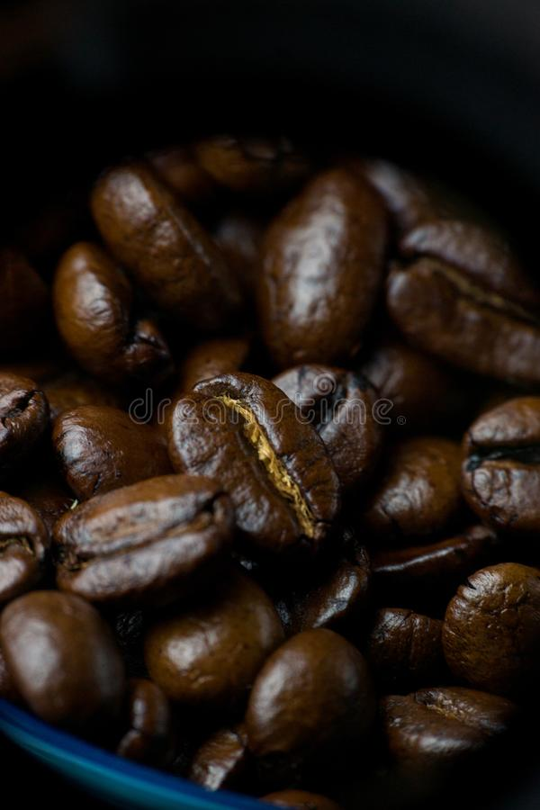 Aromatic coffee beans dark roast in a blue bowl macro photo. Vertical royalty free stock photo