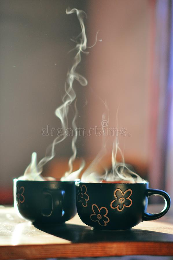 Aromatic coffee in cups in the morning sun stock photography