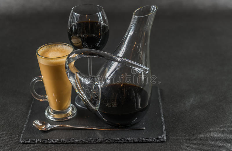 Aromatic coffee latte with red wine in a carafe and glass, teaspoon whole black stone plate. Drinks set stock photos