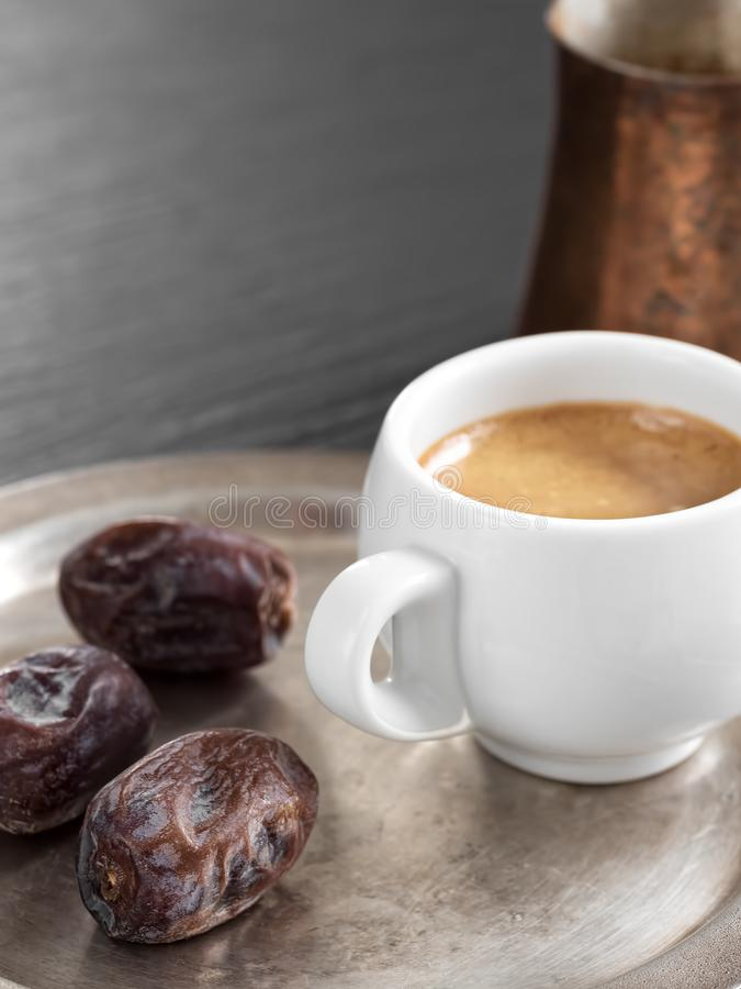 Aromatic coffee and oriental dates in a metal plate on a black stone table. In the background is a cezve. Close-up royalty free stock image