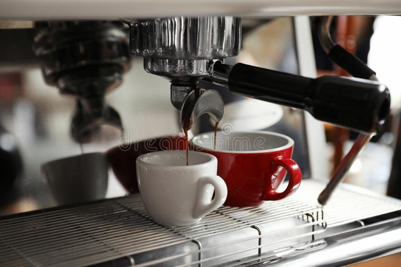 Aromatic coffee pouring into cups from modern machine stock photos