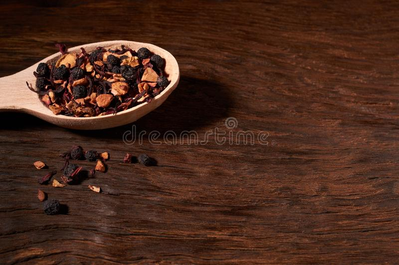 Aromatic dry tea with fruits and petals in spoon, on wooden background. Concept of cosiness. Aromatic dry tea with fruits and petals in spoon, on wooden royalty free stock photo