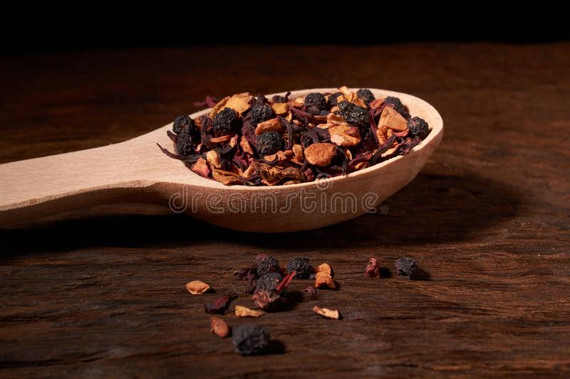 Aromatic dry tea with fruits and petals in spoon, on wooden background. Concept of cosiness. Aromatic dry tea with fruits and petals in spoon, on wooden royalty free stock images
