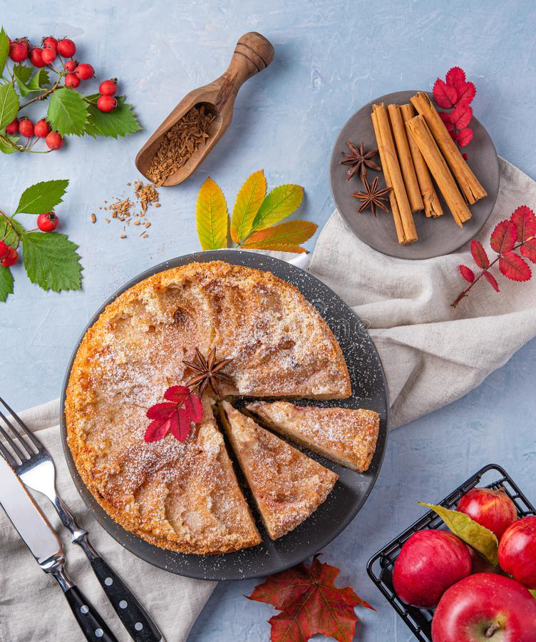 Aromatic homemade apple pie with red apple and cinnamon on wood blue table autumn. Top view royalty free stock photo