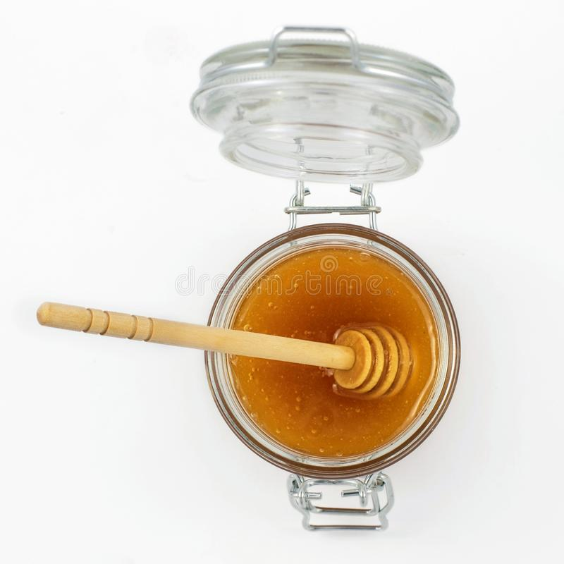 Aromatic honey with dipper into jar isolated on white background. Top view stock photo