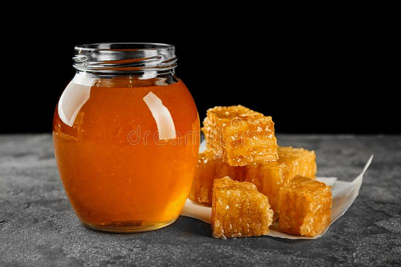 Aromatic honey in jar and honeycombs. On table stock photo