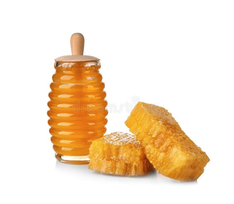 Aromatic honey in jar and honeycombs. On white background royalty free stock photo