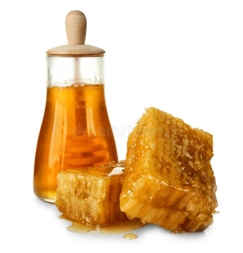 Aromatic honey in jar and honeycombs. On white background stock image