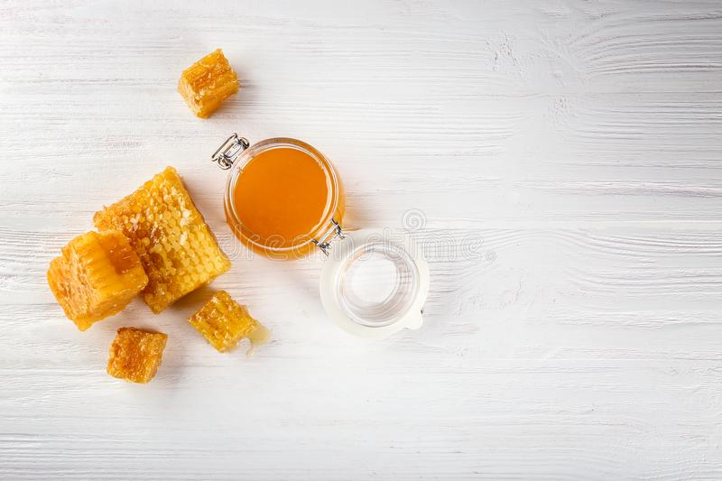 Aromatic honey in jar and honeycombs. On wooden background stock photos