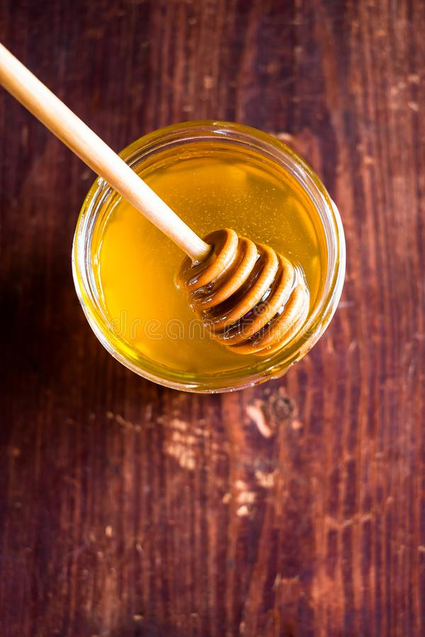 Aromatic honey with wooden honey dipper in a jar on a wooden table, selective focus, closeup. Healthy and organic food option. Ima stock photo