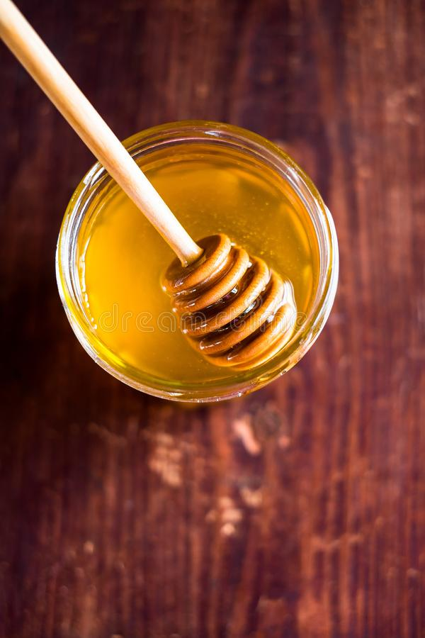 Aromatic honey with wooden honey dipper in a jar on a wooden table, selective focus, closeup. Healthy and organic food option. Ima royalty free stock photography