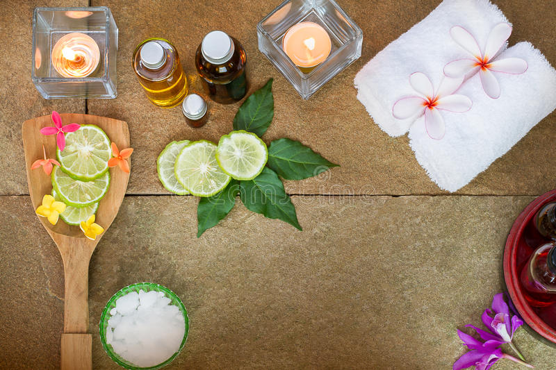 Aromatic oil, burned candle, pink yellow, orange flowers, green leaves, sliced lime, white towel on vintage grunge stone royalty free stock image