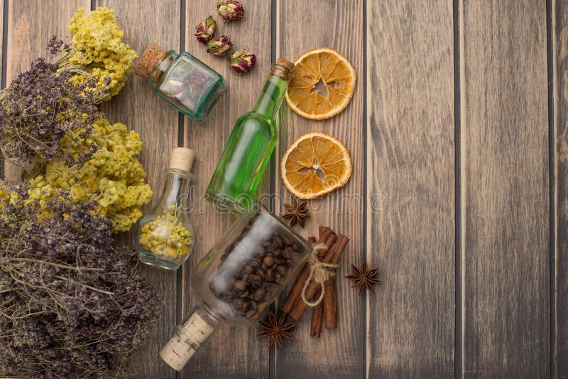 Aromatic oil, coffee grains, the aroma of grass in glass bottles, on a wooden background, with an empty space for the inscription. The concept of body care and royalty free stock images