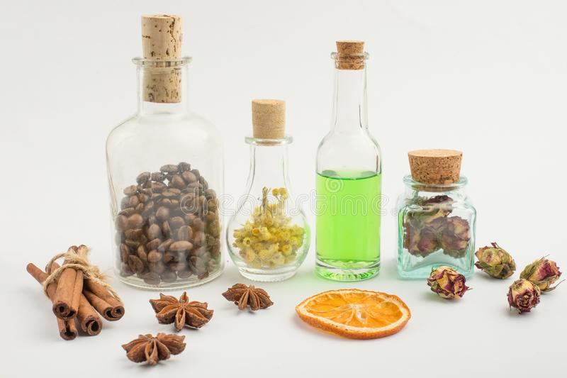 Aromatic oil, coffee grains, aroma herbs in glass bottles, on a light background. The concept of body care and beauty.  royalty free stock photo