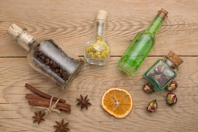 Aromatic oil, grains of coffee, aroma of grass in glass bottles, on a wooden background. The concept of body care and beauty.  royalty free stock photography