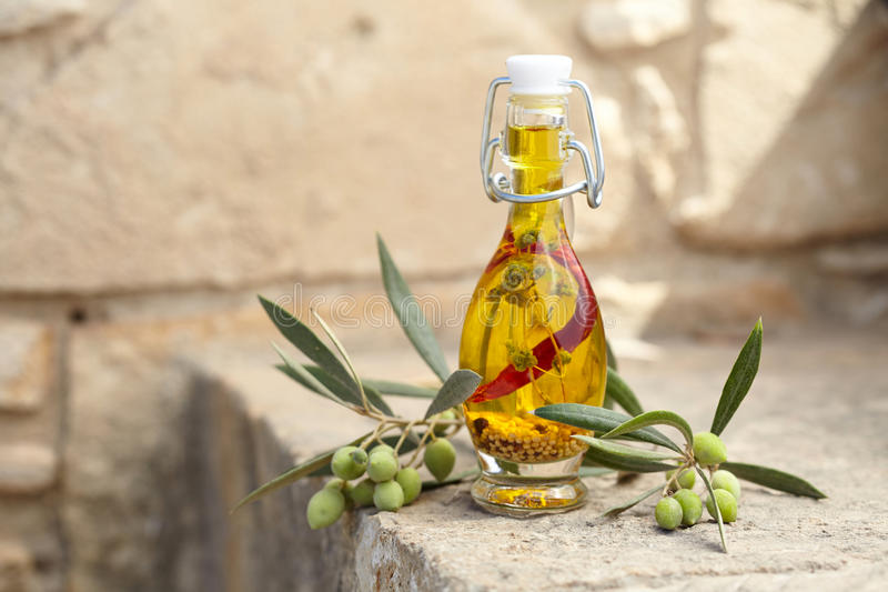 Aromatic olive oil. In a bottle with herb, pepper and mustard seeds stock photo