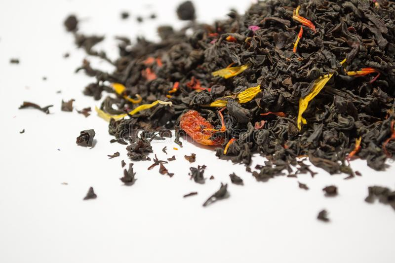 Aromatic, pungent, black tea with dry berries and flowers on white backround. royalty free stock photos