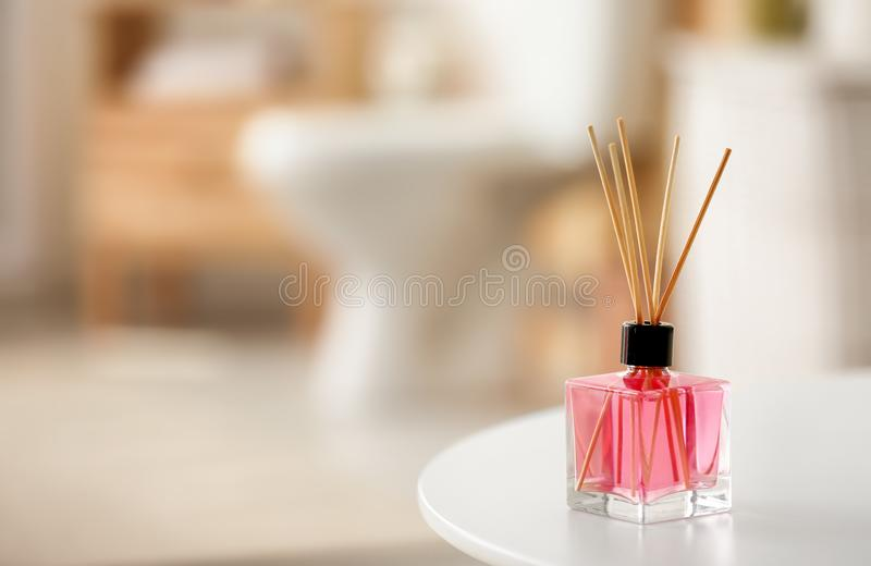 Aromatic reed air freshener on table. Against blurred background royalty free stock images