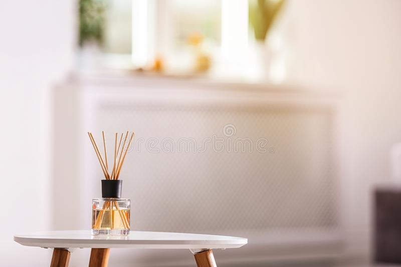 Aromatic reed air freshener on table. Against blurred background royalty free stock photography