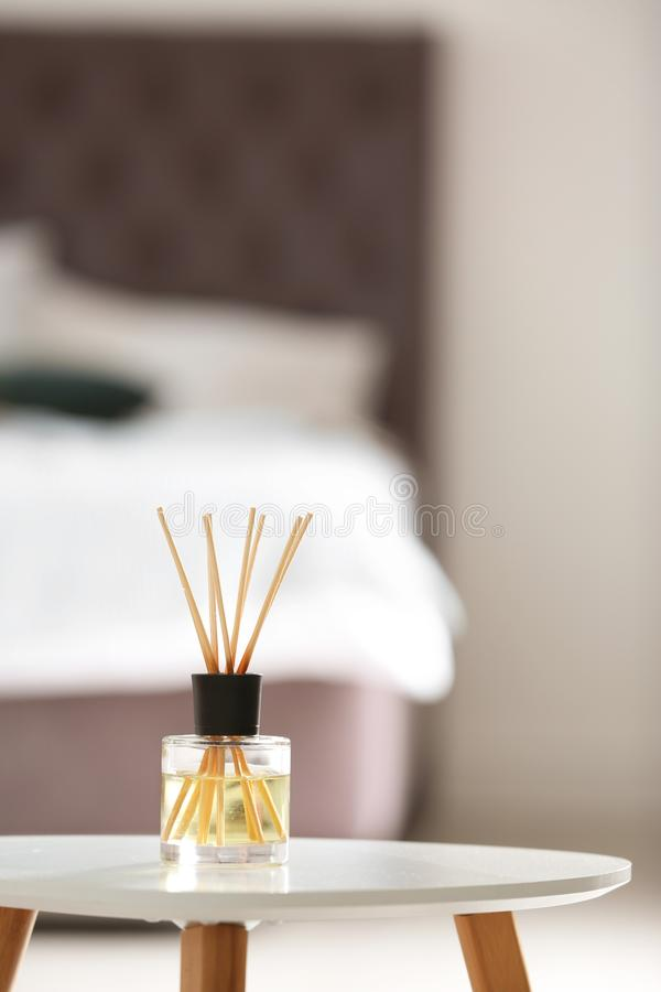 Aromatic reed air freshener on table. Against blurred background stock image