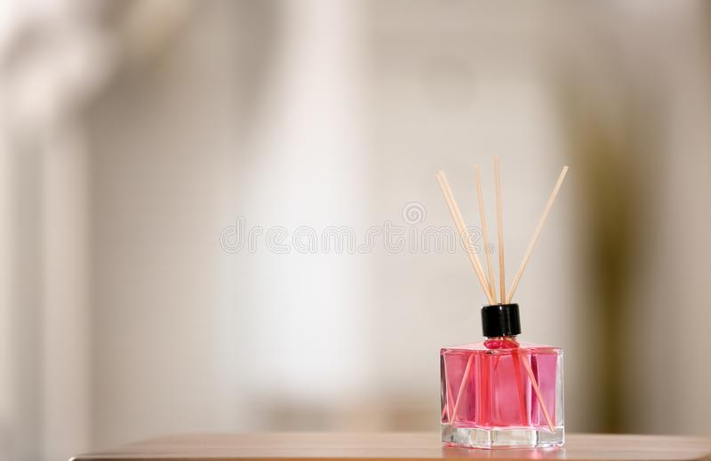 Aromatic reed air freshener on table. Against blurred background royalty free stock image
