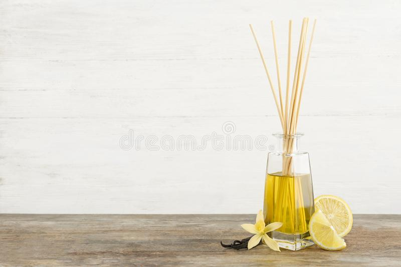 Aromatic reed freshener, lemon and vanilla on wooden table against light background. Space for text royalty free stock images