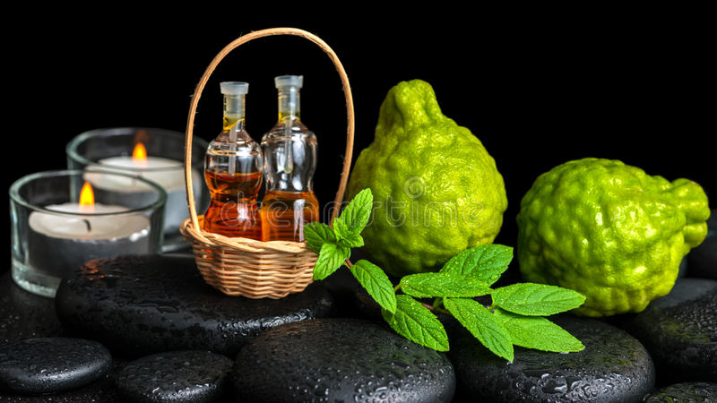 Aromatic spa concept of bergamot fruits, fresh mint, candles an. D bottles essential oil in basket on zen black stones with dew royalty free stock images