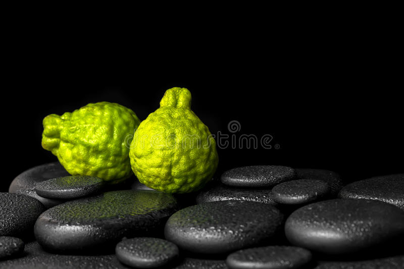 Aromatic spa concept of bergamot fruits on zen basalt black stones with dew, closeup royalty free stock photo