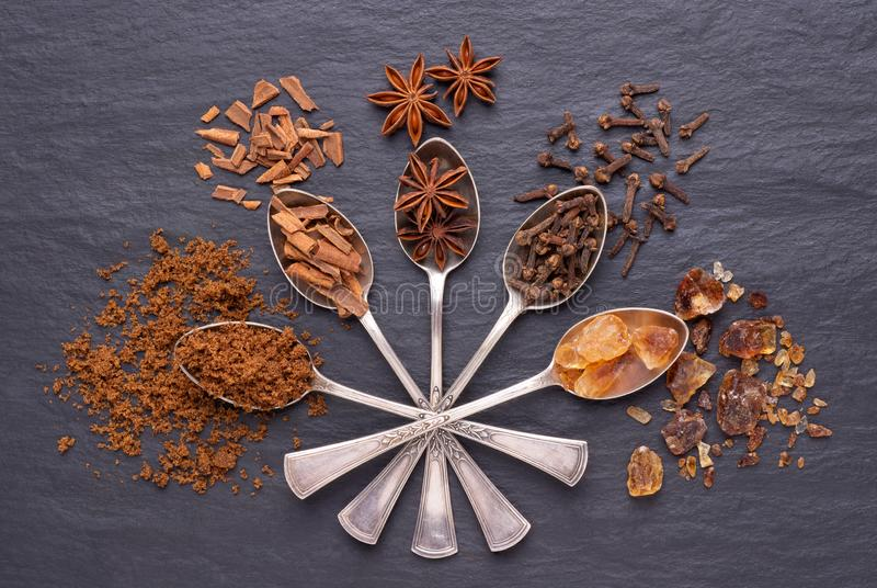 Aromatic spices and brown sugar in silver spoons on black stone background stock photography