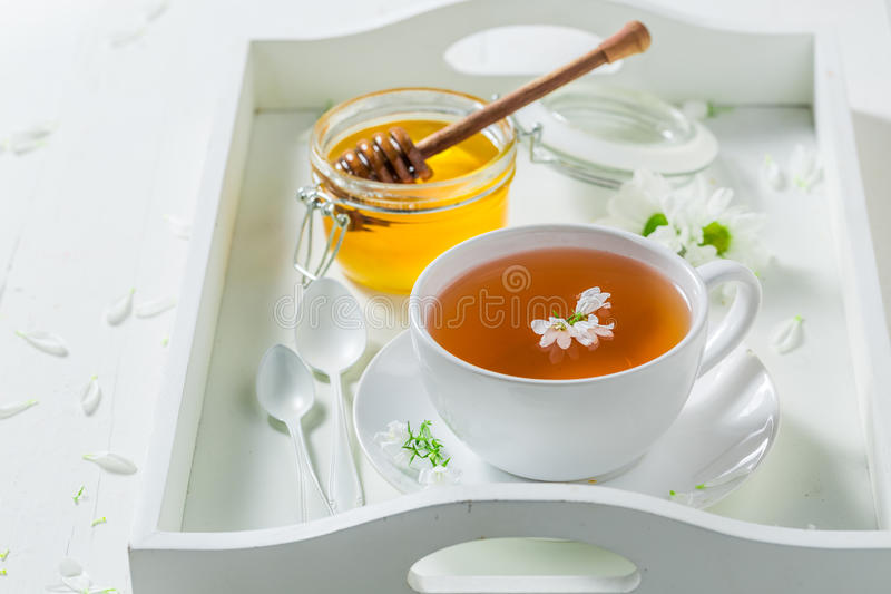 Aromatic tea with honey with spring flowers. On wooden table royalty free stock photography